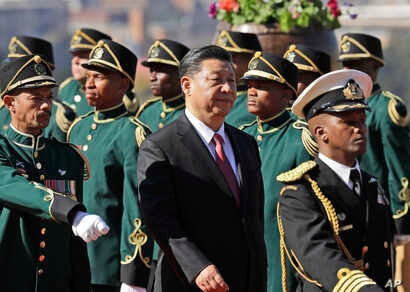 Chinese President Xi Jinping, center, inspects the honor guard during an official welcoming ceremony at the government's Union Buildings in Pretoria, South Africa, July 24, 2018.