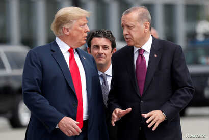 FILE - U.S. President Donald Trump and Turkish President Recep Tayyip Erdogan converse at the start of a NATO summit in Brussels, Belgium, July 11, 2018.