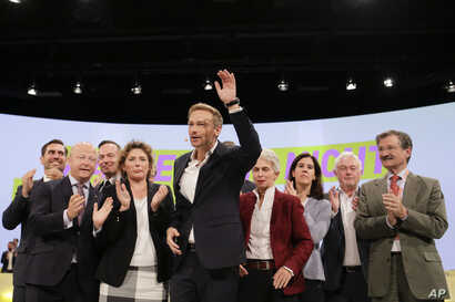 Christian Lindner, front, chairman of the German Liberal Party (FDP), waves as he receives the applause after his speech during a party's convention in Berlin, Sept. 17, 2017,