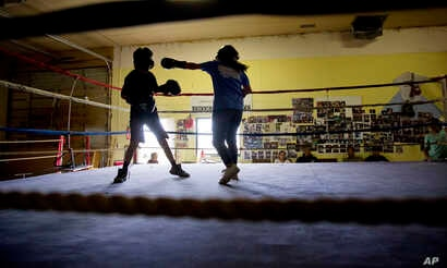 """Beatrice Kipp, 13, right, spars with Timmy Sellars, 14, at the Blackfeet Native Boxing Club on the Blackfeet Indian Reservation in Browning, Mont., July 14, 2018. """"I'm protective of our children because of human trafficking,"""" said Frank Kipp who teac..."""