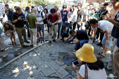 Reporters take pictures at the site of a blast outside the U.S. embassy in Beijing, China, July 26, 2018.