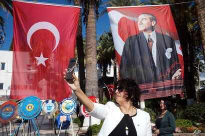 Photo taken on Oct. 28, 2018 shows a Turkish woman taking a selfie in front of a poster of Mustafa Kemal Ataturk, Turkey's founder, in Bodrum, Turkey, a day before thousands of army officers, soldiers, teachers, politicians, including Turkey's Presid...