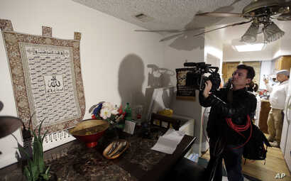 A journalist videotapes a wall tapestry displaying religious writing in the living room of an apartment in Redlands, Calif., shared by San Bernardino shootings suspects Syed Farook and his wife, Tashfeen Malik, Dec. 4, 2015.