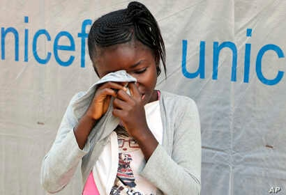 Little 11-year-old German Umba, whose father died in May of Ebola and who is being monitored by the U.N. for potential signs of infection along with her 6-year-old brother, hides her face in her shirt, sobbing, outside her classroom in Mbandaka, Cong...