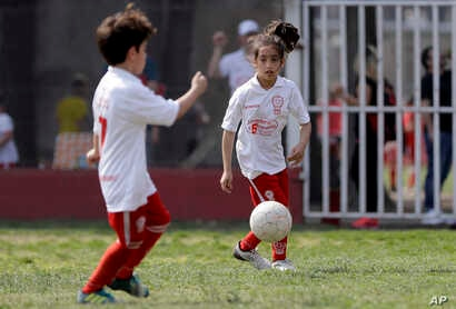 Candelaria Cabrera controls the ball during a match between her team, Huracan, and Alumni, in Chabaz, Argentina, Sept. 8, 2018.