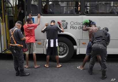 FILE - Police search bus commuters on their way to Copacabana beach in Rio de Janeiro, Brazil, Sept. 26, 2015.