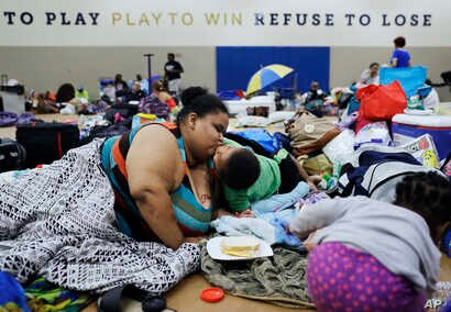 Annette Davis kisses her son Darius, 3, while staying at a shelter in Miami after evacuating from their home in Florida City, Fla., ahead of Hurricane Irma, Sept. 9, 2017.