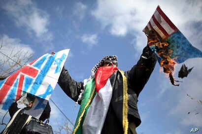 A Palestinian protester burns mock American and British flags as thousands of employees of the U.N agency for Palestinian refugees demonstrate in support of their organization following U.S. funding cuts in Gaza City, Jan. 29, 2018.
