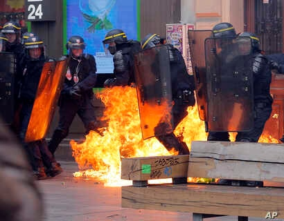 Leftist protesters throw a petrol bomb at riot policemen during clashes in Paris, France, Sept. 15, 2016.
