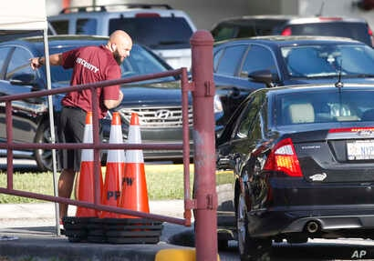 A security guard directs a car outside Marjory Stoneman Douglas High School in Parkland, Fla., Aug. 15, 2018.