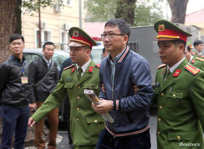 PetroVietnam's former chairman Trinh Xuan Thanh is escorted by police to the court in Hanoi, Vietnam, Jan. 8, 2018. VNA/Doan Tan via REUTERS