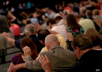 People pray during the Southern Baptist Convention annual meeting, June 13, 2017, in Phoenix.