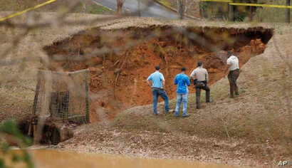 Lafayette County authorities oversee a break in the Audubon Dam in the North Point subdivision in Oxford, Miss., Feb. 23, 2019.