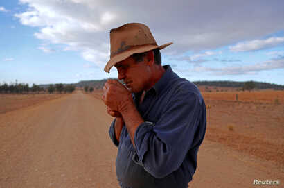 Farmer Ash Whitney lights a cigarette as he stands in the middle of a road that divides his drought-affected property, located west of the town of Gunnedah, in northwestern New South Wales in Australia, June 3, 2018.