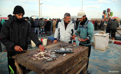 Men clean fish at a market in Gaza City, after Israel expanded fishing zone for Palestinians, April 2, 2019.