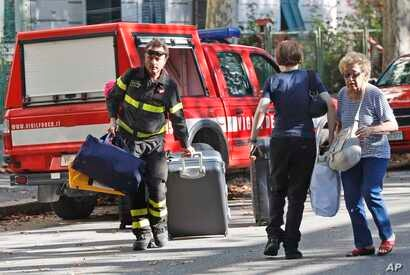 A firefighter pulls a suitcase and carries bags as he accompanies residents to get their belongings from their homes, in Genoa, Italy, Aug. 16, 2018.