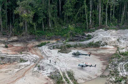 In this May 4, 2018 photo released by Ibama, the Brazilian Environmental and Renewable Natural Resources Institute, members of a specialized inspection group of Ibama walk with their weapons up through an area affected by illegal mining, after landin...