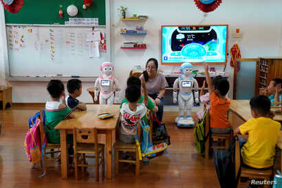 An iPal couple social robots help teach children at a kindergarten in Suzhou, Jiangsu province, China, July 4, 2018. Designed to offer education, care and companionship to children and the elderly, the 3.5-feet tall humanoid robots come in two gender...
