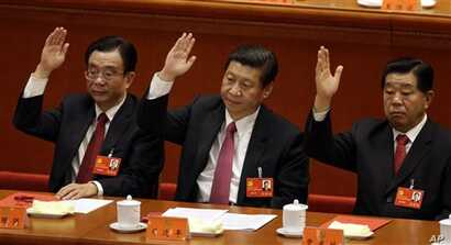 Chinese vice President Xi Jinping, center, Central Commission for Discipline Inspection head He Guoqiang, left, and Chinese People's Political Consultative Conference Chairman Jia Qinglin raise their hands to show approval for a work report during th...