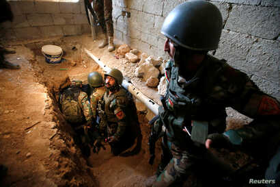 Peshmerga forces inspect a tunnel used by Islamic State militants in the town of Bashiqa, after it was recaptured from the Islamic State, east of Mosul, Iraq, Nov. 12, 2016.