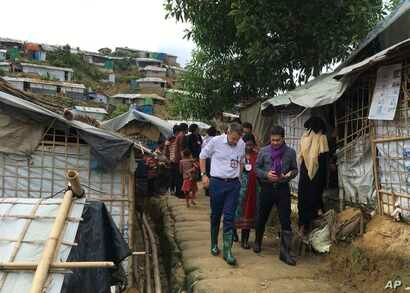 International Committee of the Red Cross President Peter Maurer, foreground and left, visits a Rohingya refugee camps in Cox's Bazar, July 1, 2018.