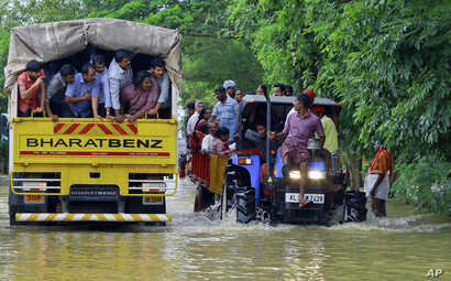 Flood affected people are rescued in a tractor, right as volunteers go for rescue work in a truck, left, at Kainakary in Alappuzha district, Kerala state, India, Aug. 17, 2018.