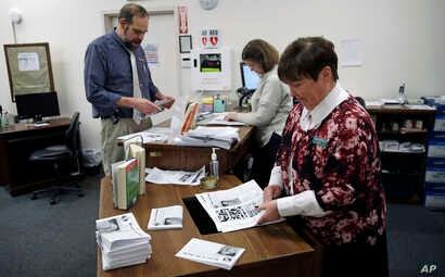 "Librarian Thelma Tracy, right, folds editions of the ""Weare in the World"" with her co-workers at the public library in Weare, New Hampshire., Jan. 22, 2018."