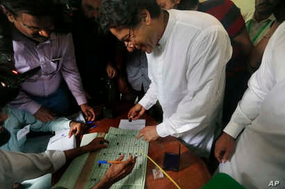 Pakistani politician Imran Khan, center, chief of Pakistan Tehreek-e-Insaf party, casts his vote at a polling station for the parliamentary elections in Islamabad, Pakistan, July 25, 2018.