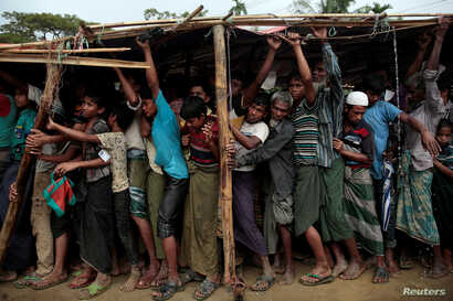Rohingya refugees jostle as they line up for a blanket distribution under heavy rainfall at the Balukhali camp near Cox's Bazar, Bangladesh, Dec. 11, 2017.