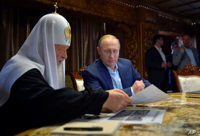 Russian President Vladimir Putin, with Russian Orthodox Patriarch Kirill, left, speak in the library of the Russian monastery St. Panteleimon at Karyes, on Mount Athos, Greece, May 28, 2016.