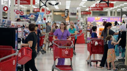 FILE - Shoppers make their way through a Target store in Dallas, Texas, Oct. 13, 2017.