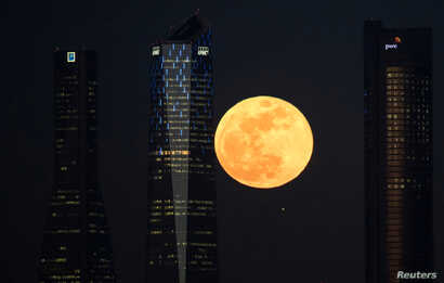 """A full moon """"supermoon"""" rises in between four towers in a skyscrapers area in Madrid, Spain, January 31, 2018."""