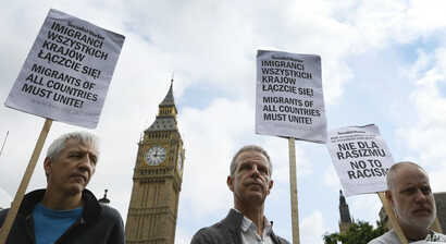 FILE - Demonstrators supporting Polish workers hold banners at a rally in Westminster, London, Aug. 20, 2015. Britain's new government wants to see curbs on employers hiring foreign workers and tightening tests on companies that want to recruit overs...