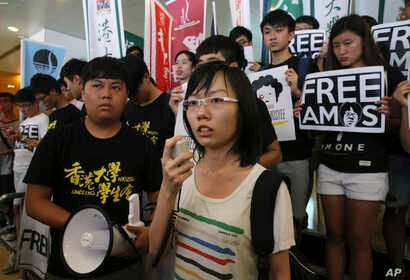 Singaporean protester Han Hui-hui, center, accompanied by Hong Kong students, speaks during a protest outside the Singapore Consulate in Hong Kong, June 30, 2015 to urge Singapore government to release teen blogger Amos Yee. Yee had been found guilty...