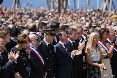 French Prime Minister Manuel Valls (C), President of the Provence Alpes Cote d'Azur (PACA) region Christian Estrosi and Prince Albert II of Monaco stand at the Monument du Centenaire during a minute of silence on the third day of national mourning to...