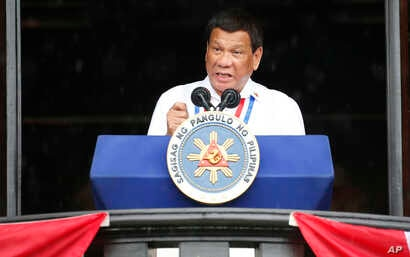 Philippine President Rodrigo Duterte gestures while addressing the crowd after leading the flag-raising rites at the 120th Philippine Independence Day celebration at the Emilio Aguinaldo Shrine at Kawit, Cavite province south of Manila, June 12, 2018
