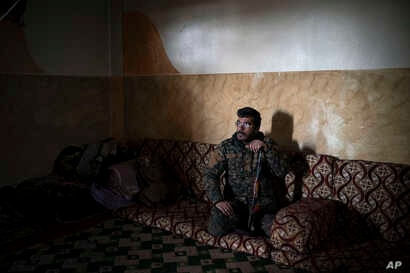 Dia Hassakeh, 45, a fighter in the Kurdish-led U.S-backed Syrian Democratic Forces, looks out of a building in Baghouz, Syria, Feb. 18, 2019.