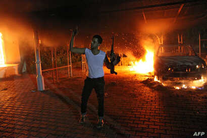 An armed man waves his rifle as buildings and cars are engulfed in flames after being set on fire inside the US consulate compound in Benghazi late on September 11, 2012.