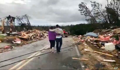 People walk amid debris in Lee County, Ala., after what appeared to be a tornado struck in the area Sunday, March 3, 2019.