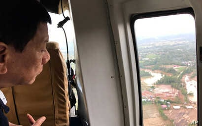 Philippine President Rodrigo Duterte looks at damage after Tropical Storm Kai-Tak hit the island province of Biliran, central Philippines, Dec. 18, 2017. On Wednesday, the coast guard reported a ferry had capsized in a new storm.