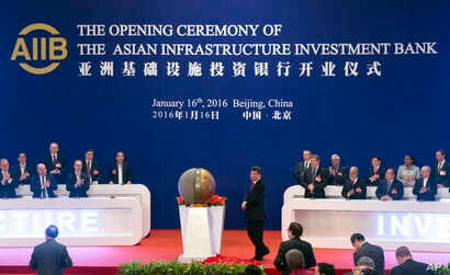FILE - Representatives of the founding nations of the Asian Infrastructure Investment Bank (AIIB) applaud as Chinese President Xi Jinping, center, unveils a sculpture during the opening ceremony of the AIIB in Beijing, Jan. 16, 2016.
