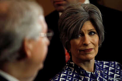 U.S. Sen. Joni Ernst, R-Iowa, looks at Senate Majority Leader Mitch McConnell of Kentucky during a news conference following leadership elections at the U.S. Capitol in Washington, Nov. 14, 2018.