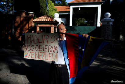 "A Venezuelan demonstrator holds a banner that reads ""[President Nicolas] Maduro doesn't govern Venezuela"" outside the Olivos Presidential Residence, in Buenos Aires, Argentina, March 1, 2019."