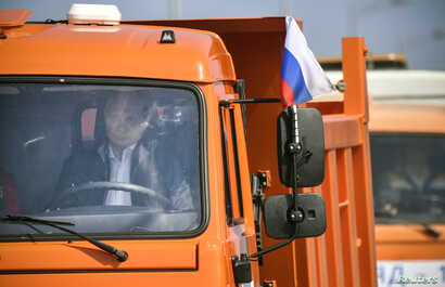 Russian President Vladimir Putin drives a Kamaz dump truck during a ceremony opening the Kerch Strait Bridge, which connects the Russian mainland with territorially disputed Crimea, May 15, 2018.
