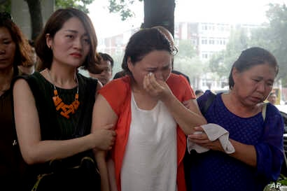 Fan Lili, center, the wife of imprisoned activist  Gou Hongguo, is escorted by Li Wenzu, left, the wife of imprisoned lawyer Wang Quanzhang, and another woman as they stage a protest outside the Tianjin No. 2 Intermediate People's Court in Tianjin, C...