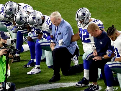 FILE - The Dallas Cowboys, led by owner Jerry Jones, center, take a knee before the national anthem at an NFL football game against the Arizona Cardinals, in Glendale, Ariz., Sept. 25, 2017.
