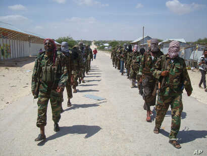FILE - members of Somalia's al-Shabab militant group patrol on foot on the outskirts of Mogadishu, Somalia, March 5, 2012. Somalia now says says al-Shabab militants are plotting to supply uranium to Iran.