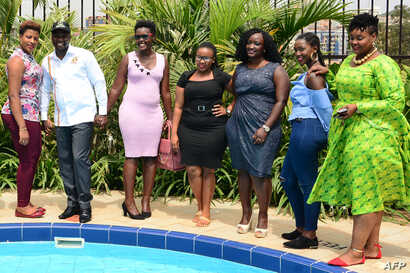 Uganda's Minister for Tourism Godfrey Kiwanda (2-L) poses next to participants during the launch of the Miss Curvy beauty contest in capital Kampala, Feb. 5, 2019.