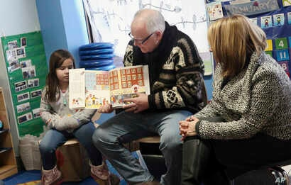 Gov. Tim Walz, top, reads a book to children at People Helping People, a shelter for families experiencing homelessness amid extreme cold weather conditions in Minnesota, Jan. 29, 2019, in Minneapolis, accompanied by Lt. Gov. Peggy Flanagan, right.