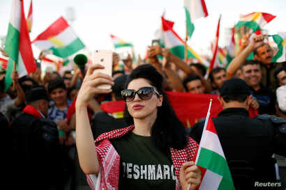 A Kurdish woman takes a selfie to show support for the upcoming September 25th independence referendum in Erbil, Iraq Sept. 22, 2017.